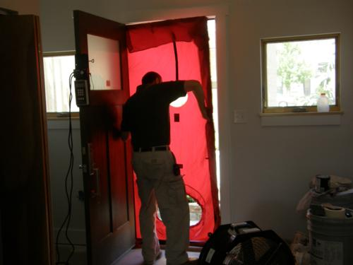 A blower door test being performed
